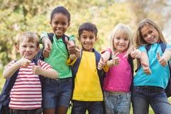 Χαμογελώντας συμμαθητές που κάνουν τους αντίχειρες μέχρι τη κάμερα στοκ φωτογραφία με δικαίωμα ελεύθερης χρήσης