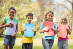 Χαμογελώντας συμμαθητές που κρατούν τα σημειωματάρια στοκ φωτογραφία με δικαίωμα ελεύθερης χρήσης