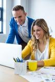 Χαμογελώντας συνάδελφοι που χρησιμοποιούν το lap-top στην αρχή στοκ φωτογραφία