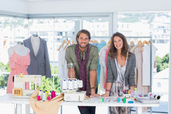 Χαμογελώντας σχεδιαστές μόδας που κλίνουν στο γραφείο Στοκ Εικόνες