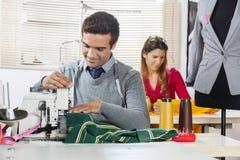 Χαμογελώντας σχεδιαστές μόδας που ράβουν τα υφάσματα στο ράψιμο του εργοστασίου Στοκ Φωτογραφίες