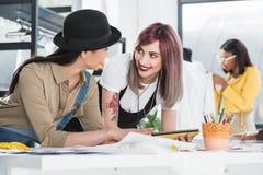 Χαμογελώντας σχεδιαστής μόδας που εργάζεται με τα σκίτσα και την ψηφιακή ταμπλέτα Στοκ φωτογραφία με δικαίωμα ελεύθερης χρήσης