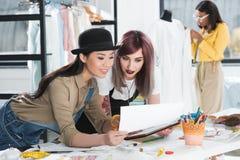 Χαμογελώντας σχεδιαστής μόδας που εργάζεται με τα σκίτσα και την ψηφιακή ταμπλέτα Στοκ Φωτογραφία