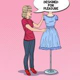 Χαμογελώντας σχεδιαστής μόδας στην εργασία με το φόρεμα σε ένα μανεκέν clothing dummies female industry inside store textile wome ελεύθερη απεικόνιση δικαιώματος