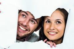 Χαμογελώντας σχισμένο έγγραφο ζευγών που κρυφοκοιτάζουν έξω Στοκ φωτογραφία με δικαίωμα ελεύθερης χρήσης