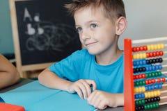 Χαμογελώντας σχολικό αγόρι που εργάζεται στην εργασία math Στοκ φωτογραφία με δικαίωμα ελεύθερης χρήσης