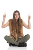 Χαμογελώντας τα πόδια συνεδρίασης γυναικών που διασχίζονται και δείχνοντας επάνω Στοκ Εικόνες