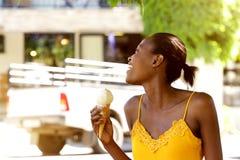 Χαμογελώντας τον αφρικανικό κώνο παγωτού εκμετάλλευσης γυναικών έξω Στοκ φωτογραφία με δικαίωμα ελεύθερης χρήσης