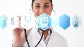Χαμογελώντας το στηθοσκόπιο εκμετάλλευσης γιατρών που παρουσιάζει διάφορα εικονίδια φιλμ μικρού μήκους