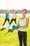 Χαμογελώντας φίλαθλη γυναίκα μπροστά από τους φίλους που κάνουν τις ασκήσεις στοκ εικόνες με δικαίωμα ελεύθερης χρήσης