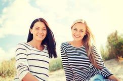 Χαμογελώντας φίλες που έχουν τη διασκέδαση στην παραλία στοκ εικόνες