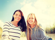 Χαμογελώντας φίλες που έχουν τη διασκέδαση στην παραλία στοκ φωτογραφίες