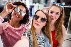 Χαμογελώντας φίλες που φορούν τα μοντέρνα γυαλιά ηλίου που έχουν το χρόνο διασκέδασης που παίρνει selfie με το κινητό τηλέφωνο κά στοκ φωτογραφία με δικαίωμα ελεύθερης χρήσης