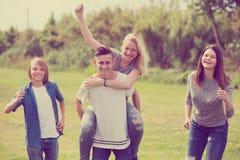 Χαμογελώντας φίλοι που έχουν τη διασκέδαση και το τρέξιμο στοκ φωτογραφία