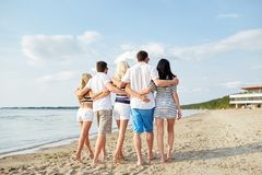 Χαμογελώντας φίλοι που αγκαλιάζουν και που περπατούν στην παραλία Στοκ Φωτογραφία