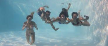 Χαμογελώντας φίλοι που εξετάζουν τη κάμερα υποβρύχιοι στην πισίνα στοκ εικόνα