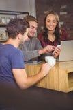 Χαμογελώντας φίλοι που εξετάζουν το smartphone στοκ εικόνα με δικαίωμα ελεύθερης χρήσης