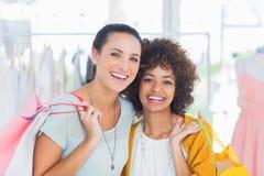 Χαμογελώντας φίλοι που κρατούν τις τσάντες αγορών στοκ εικόνες με δικαίωμα ελεύθερης χρήσης