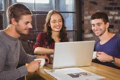 Χαμογελώντας φίλοι που πίνουν τον καφέ και που εξετάζουν το lap-top Στοκ Φωτογραφία