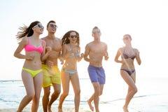 Χαμογελώντας φίλοι στα γυαλιά ηλίου που τρέχουν στην παραλία Στοκ εικόνα με δικαίωμα ελεύθερης χρήσης