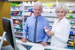 Χαμογελώντας φαρμακοποιοί που στέκονται στο φαρμακείο στοκ εικόνες