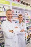 Χαμογελώντας φαρμακοποιός και ο εκπαιδευόμενός του με τα όπλα που διασχίζονται Στοκ Φωτογραφίες