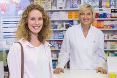 Χαμογελώντας φαρμακοποιός και πελάτης που συζητούν ένα προϊόν στοκ φωτογραφίες