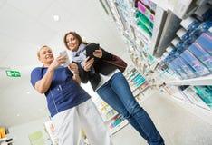 Χαμογελώντας φαρμακοποιός που εξηγεί τις λεπτομέρειες προϊόντων στοκ εικόνες με δικαίωμα ελεύθερης χρήσης