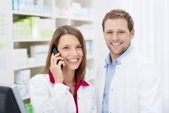 Χαμογελώντας φαρμακοποιός που κουβεντιάζει στο τηλέφωνο στοκ εικόνα με δικαίωμα ελεύθερης χρήσης