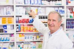 Χαμογελώντας φαρμακοποιός που παίρνει την ιατρική από το ράφι στοκ φωτογραφίες με δικαίωμα ελεύθερης χρήσης