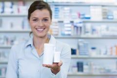 Χαμογελώντας φαρμακοποιός που παρουσιάζει εμπορευματοκιβώτιο ιατρικής στο φαρμακείο στοκ φωτογραφίες