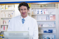 Χαμογελώντας φαρμακοποιός που στέκεται στο μετρητή στο φαρμακείο στοκ φωτογραφία με δικαίωμα ελεύθερης χρήσης