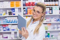 Χαμογελώντας φαρμακοποιός που χρησιμοποιεί το PC ταμπλετών στοκ εικόνες με δικαίωμα ελεύθερης χρήσης