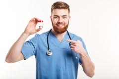 Χαμογελώντας φιλικός φαρμακοποιός που δείχνει το δάχτυλο στο μπουκάλι με τις ταμπλέτες Στοκ φωτογραφία με δικαίωμα ελεύθερης χρήσης