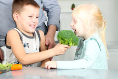 Χαμογελώντας χαριτωμένοι κόρη και γιος που δαγκώνουν ένα μπρόκολο Μικρά παιδιά που παίζουν με vegatable με τον πατέρα Στοκ φωτογραφίες με δικαίωμα ελεύθερης χρήσης