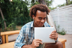Χαμογελώντας χαριτωμένος αφρικανικός νεαρός άνδρας με την ταμπλέτα που ακούει τη μουσική Στοκ φωτογραφία με δικαίωμα ελεύθερης χρήσης
