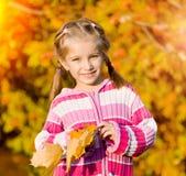 Χαμογελώντας χαριτωμένο κορίτσι ενάντια στα φύλλα στοκ φωτογραφία