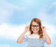 Χαμογελώντας χαριτωμένο μικρό κορίτσι με μαύρα eyeglasses Στοκ Φωτογραφίες