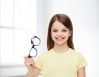 Χαμογελώντας χαριτωμένο μικρό κορίτσι που κρατά μαύρα eyeglasses Στοκ εικόνες με δικαίωμα ελεύθερης χρήσης