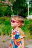 Χαμογελώντας χαριτωμένο μικρό κορίτσι στα ρόδινα γυαλιά ηλίου Στοκ εικόνες με δικαίωμα ελεύθερης χρήσης