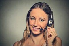 Χαμογελώντας χειριστής υποστήριξης πελατών με την κάσκα στο γκρίζο υπόβαθρο τοίχων Στοκ Εικόνες