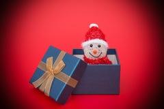 Χαμογελώντας χιονάνθρωπος Χριστουγέννων παιχνιδιών σε ένα παρόν κιβώτιο στοκ εικόνα