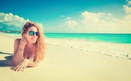 Χαμογελώντας όμορφη γυναίκα που κάνει ηλιοθεραπεία σε μια παραλία Στοκ Εικόνες