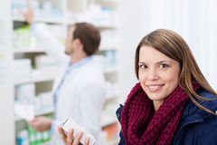 Χαμογελώντας όμορφη γυναίκα που περιμένει σε ένα φαρμακείο Στοκ εικόνες με δικαίωμα ελεύθερης χρήσης