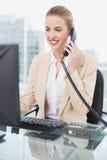 Χαμογελώντας όμορφη επιχειρηματίας που απαντά στο τηλέφωνο Στοκ Εικόνες