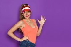 Χαμογελώντας όμορφη νέα γυναίκα που παρουσιάζει πέντε δάχτυλα Στοκ Εικόνα