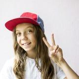 Χαμογελώντας όμορφος έφηβος κοριτσιών σε ένα καπέλο του μπέιζμπολ και μια άσπρη μπλούζα Στοκ Φωτογραφία
