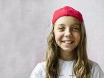 Χαμογελώντας όμορφος έφηβος κοριτσιών σε ένα καπέλο του μπέιζμπολ και μια άσπρη μπλούζα Στοκ Εικόνες