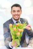 Χαμογελώντας όμορφο άτομο που δίνει την ανθοδέσμη των λουλουδιών Στοκ Φωτογραφία