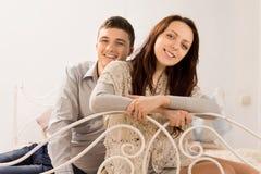 Χαμογελώντας όμορφο ζεύγος σε ένα κρεβάτι επεξεργασμένου σιδήρου στοκ φωτογραφία